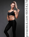 Sports girl with pumped muscles,beauty body in a tracksuit, leading a healthy lifestyle and posing 46454278