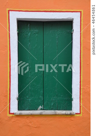 Closed window with green shutter on orange wall 46454861