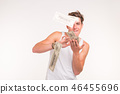Rich, fun and finance concept - handsome young man throws money over white background. 46455696