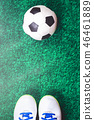 Soccer ball and cleats on green artificial turf 46461889
