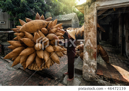 Old Vietnamese male craftsman standing with bicycle which making the traditional bamboo fish trap or weave at the old traditional house, Vietnam 46472139