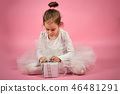 Cute little girl in tulle skirt opens a gift on a pink background 46481291