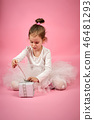 Cute little girl in tulle skirt opens a gift on a pink background 46481293