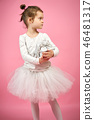Cute little girl in tulle skirt is holding a gift on a pink background 46481317