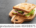 Close-up photo of a club sandwich. Sandwich with meet, prosciutto, salami, salad, vegetables 46498975