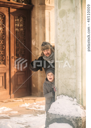 A joyful boy in a coat is playing with father in winter 46510009