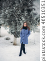 Beautiful girl in the winter outdoors. Girl is surrounded by snow-covered trees. Christmas mood. New 46510351