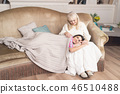 Charming girl lying on mother's knees on sofa 46510488