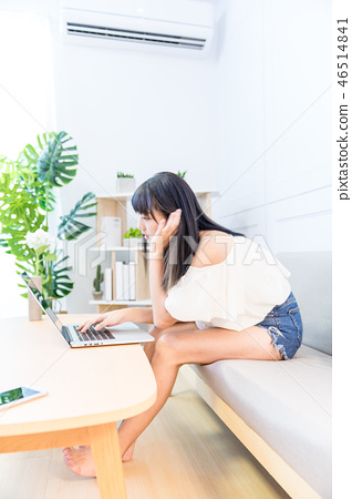 坐在地面上的一名婦女使用的手寫電動風扇。爬行的生活方式。爬行婦女的常規購買,平行使用信貸協議。 46514841