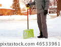 Man shoveling and removing snow in the suburb 46533961
