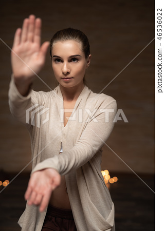 Serious lady standing alone and putting hands in front of her face 46536022