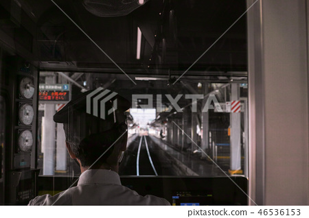 Rear view of a train driver pulling into a station 46536153