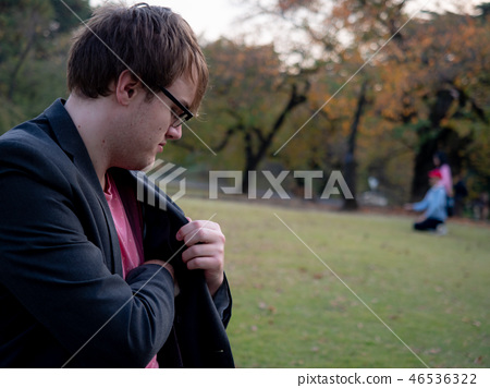 A man taking something out of his jacket pocket 46536322