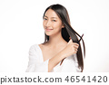 Portrait of beautiful young woman combing her hair 46541420