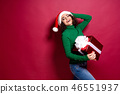 Beautiful fashion woman in santa claus hat. Warm Christmas sweater holding gift box on. 46551937