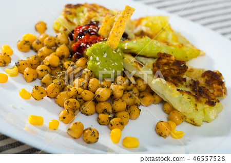 Tasty leaves of cabbage in batter and garbanzo with sauce at plate 46557528