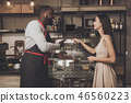 Male barista helps a girl to choose a dessert 46560223