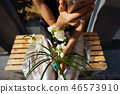 Young woman sitting with a bouquet of white flowers. 46573910