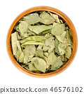 Dried whole curry leaves in wooden bowl over white 46576102