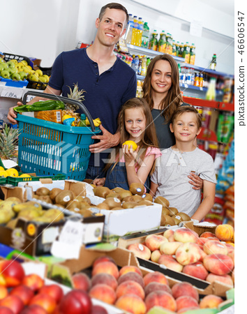 Family with two standing with cart of fresh fruits 46606547