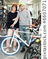 pair in helmet standing with bicycle 46607071