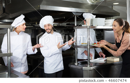 Chef of restaurant with team of cooks preparing food 46607474
