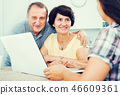 Mature couple looking at woman showing laptop 46609361