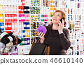 Woman with needlework accessories and talking on phone 46610140