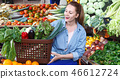 Female is looking on shelves with produts and standing with basket in the market. 46612724