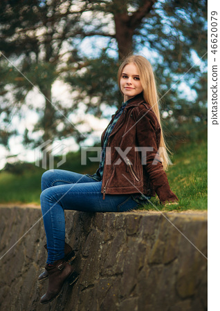 Attrective young girl sits by the embankment. Blond hair and brown jacket. Spring 46620079
