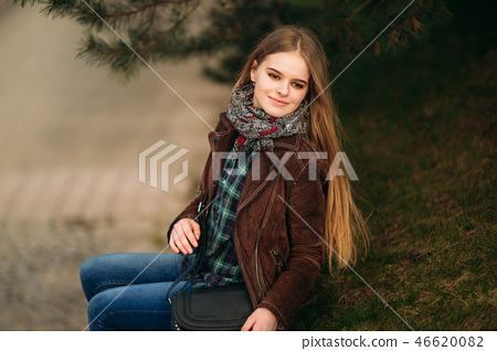 Attrective young girl sits by the embankment. Blond hair and brown jacket. Spring 46620082