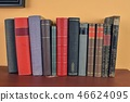 Antique books on old wooden shelf. Old books on yellow and claret background 46624095