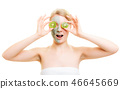 Skin care. Woman in clay mask with kiwi on face 46645669