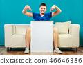 man on sofa holding blank presentation board 46646386