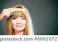Closeup woman combing her fringe with comb 46662072