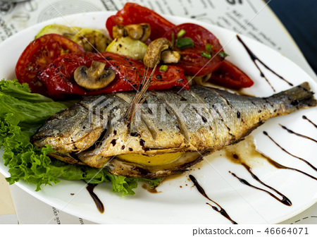 Fried fish with grilled tomatoes and lemon. Small depth of field 46664071