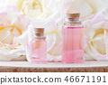 glass bottles of aroma oil and fresh rose flowers, selective focus 46671191