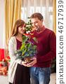 Loving couple with illuminated poinsettia flower on Christmas 46717939