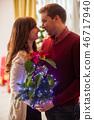 Loving couple with illuminated poinsettia flower on Christmas 46717940