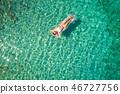 Top down view of a beautiful woman in a white bikini who is floa 46727756