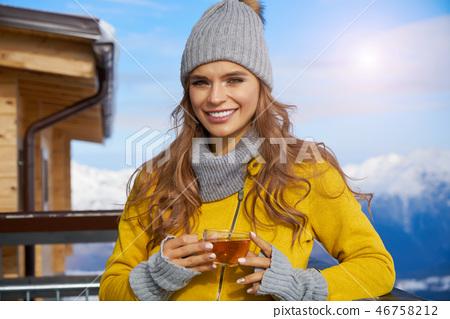 Woman drinking warm tea in the rustick wooden terrace on mountai 46758212