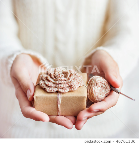 Woman in knitted sweater holding present  46761330