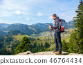Hiker young man with backpack and trekking poles standing on edge of cliff and looking at the lake 46764434