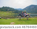 young couple of backpackers near the lake in mountains 46764460