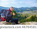 Young male hiker with backpack relaxing on top of a mountain during calm summer day. 46764581