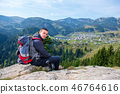 Young male hiker with backpack relaxing on top of a mountain during calm summer day. 46764616