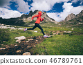 Woman trail runner jumping over small river   46789761