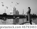 Woman wearing sunglasses standing on a boat with Taj Mahal in background. 46793463