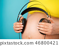 Pregnant woman holding earphones on her belly with baby, enjoying favorite music on blue background 46800421