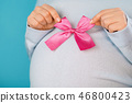 Pregnant woman holding pink bow on tummy belly background. Young girl expecting baby. Maternity 46800423